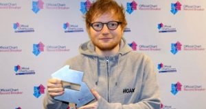 Ed Sheeran holding his number one trophy sideways so it looks more like a letterbox