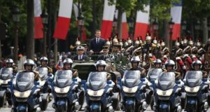 The new French president was driven in an open-top military vehicle up the Champs-Élysées