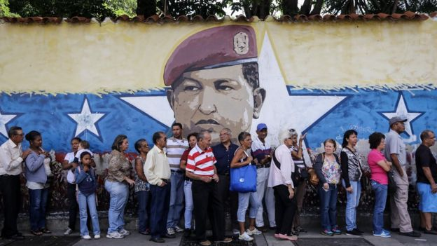 People in Caracas queue to vote next to an image of former Socialist party leader Hugo Chavez