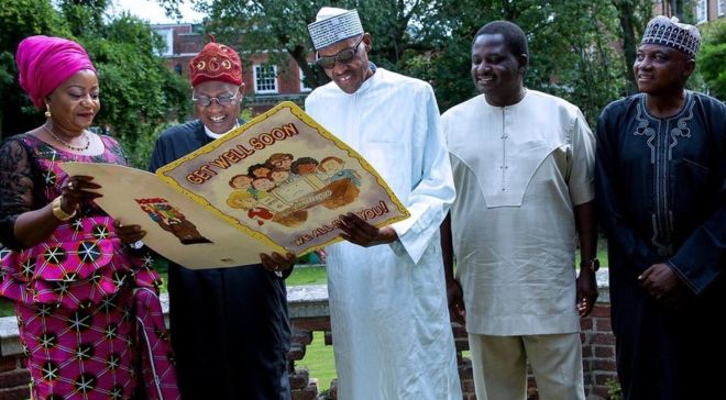 A photograph tweeted by the @NGRPresident Twitter account shows President Buhari with officials, smiling over a large get well card